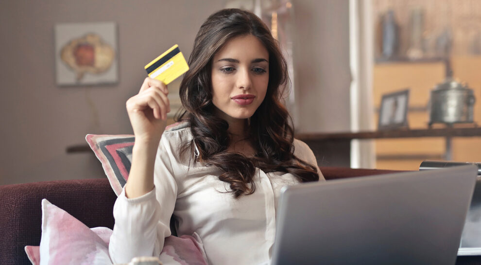 woman holding credit card and laptop symbolizing online shopping
