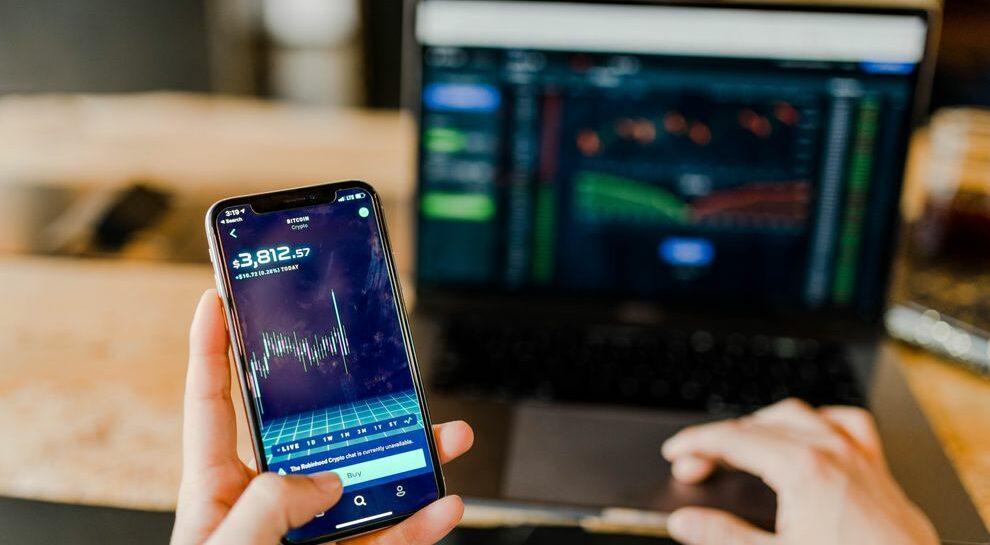 stocks on phone and laptop symbolizing fintech innovation