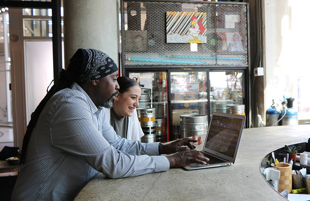 two people working on laptop symbolizing increased e-commerce demand for SMBs